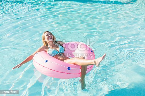 A young woman lying in an inner tube, floating in a swimming pool.