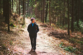 Young Caucasian woman walking in spring forest and looking around