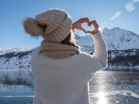 Young woman ice skating on frozen lake and making a heart with hands. winter vacations