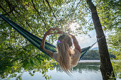 Young woman on hammock by the river making a heart shape finger frame loving travel relax concept in vacations