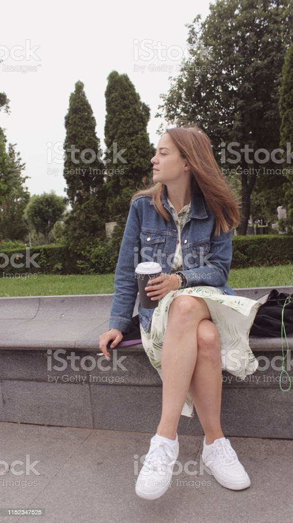 Young blond woman drinking coffee and smoking standing and sitting in...