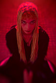 istock Young woman on her knees with devilish look in her eyes, red lights, horror concept 1339676331