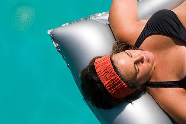 junge frau auf aufblasbare matratze im schwimmbad - elemi stock-fotos und bilder