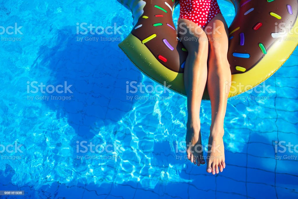 Young woman on inflatable mattress in the swimming pool stock photo