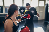 istock Young woman on kick box practice, learning from her coach while sparring with him 1210290770