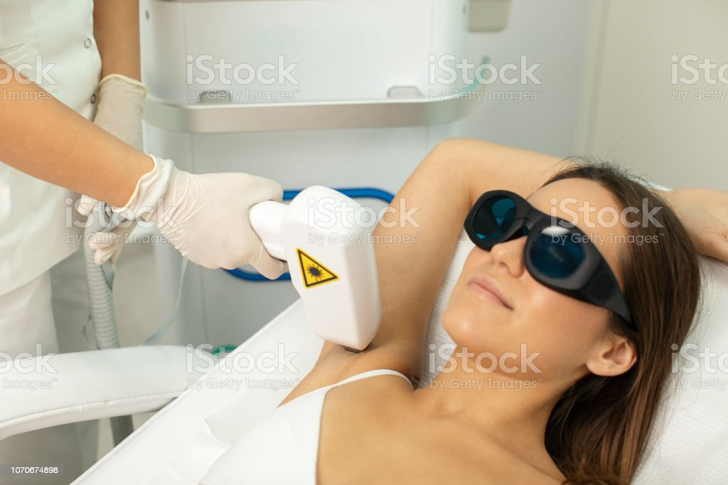 Young woman on laser hair removal treatment stock photo