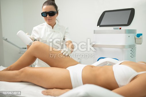 Beautiful young woman receiving laser body hair removal treatment at beauty and health clinic. Beautician is also young and concentrated. Treatment on legs