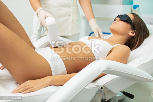 Beautiful young woman receiving laser body hair removal treatment at beauty and health clinic. Beautician is also young and concentrated. Abdomen treatment