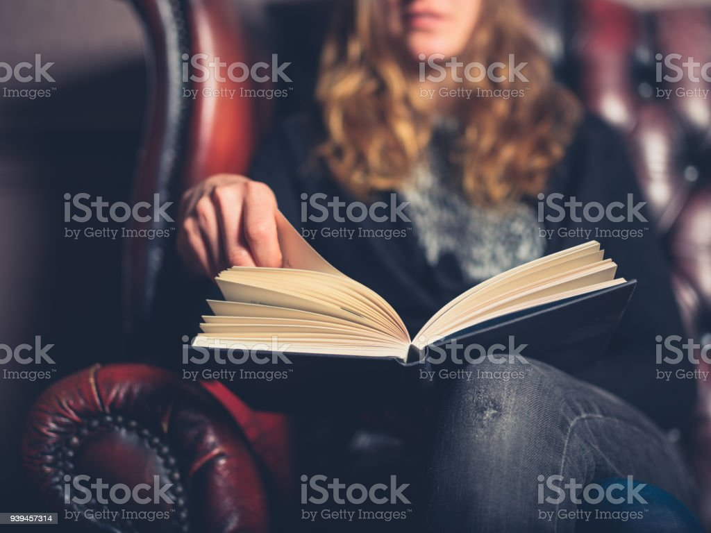 Young woman on leather sofa reading a book stock photo