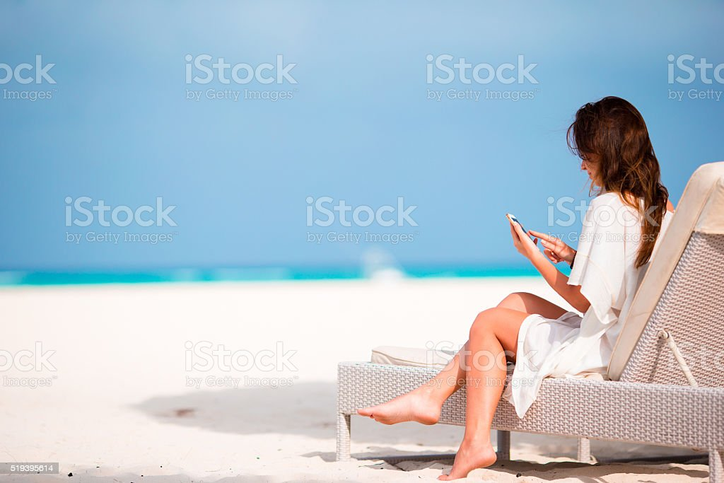 Young woman on lounger with mobile phone at the beach stock photo