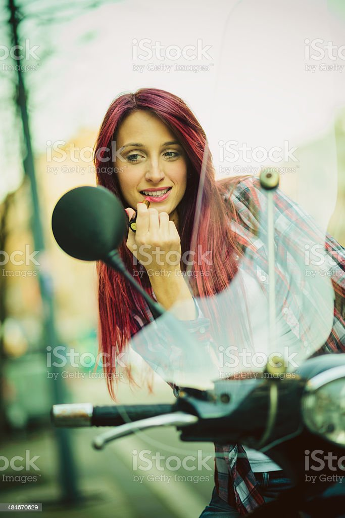 Young woman on motorcycle fixing make up stock photo