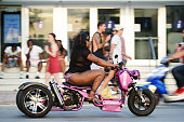 Miami - April 28, 2018: A young woman rides a three-wheel motorcycle past the tourist crowds on Ocean Drive in South Beach.