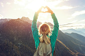 Young woman hiking on the mountain top makes a heart shape finger frame above her head to the beautiful landscape.