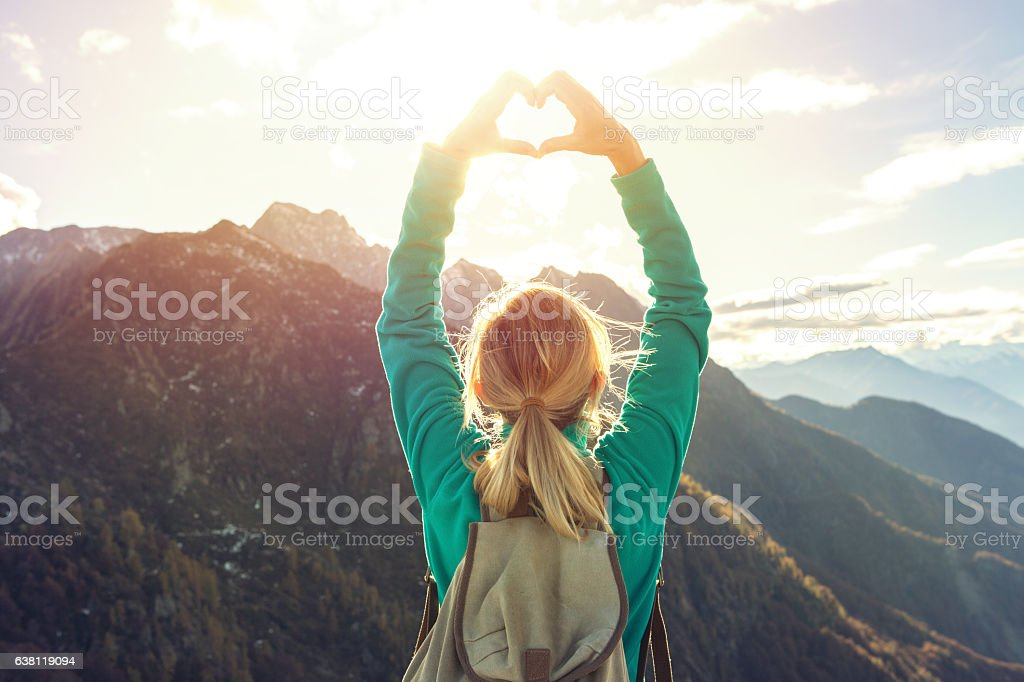 Young woman on mountain top makes heart shape finger frame stock photo