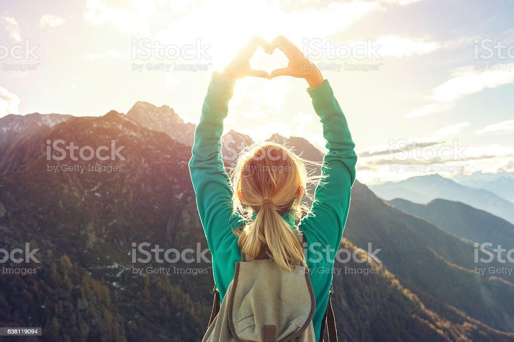 Junge Frau auf Berg top macht Herzform finger frame – Foto