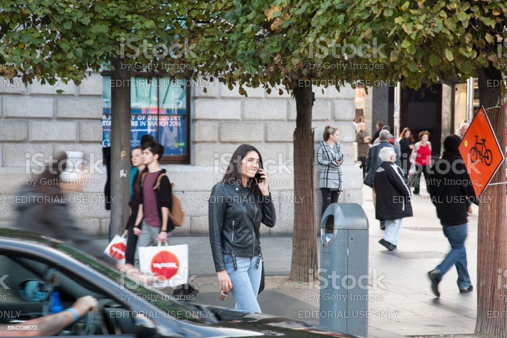 Young woman on phone at O'Connell street stock photo