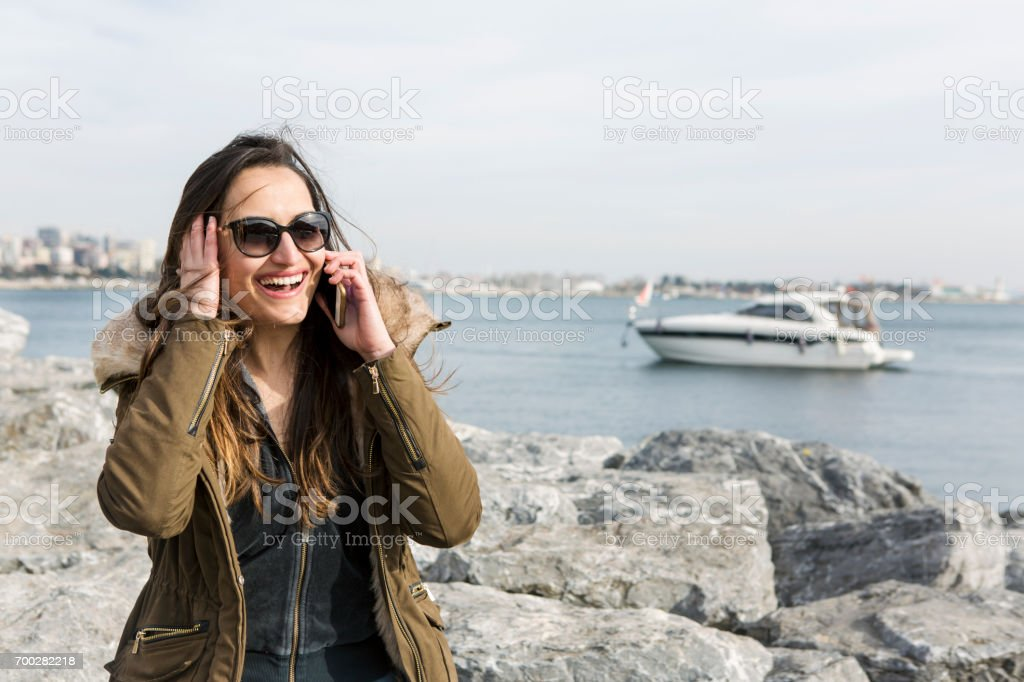 Young woman on phone laughing at the park