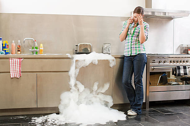 young woman on phone with overflowing dishwasher - overflowing stock photos and pictures
