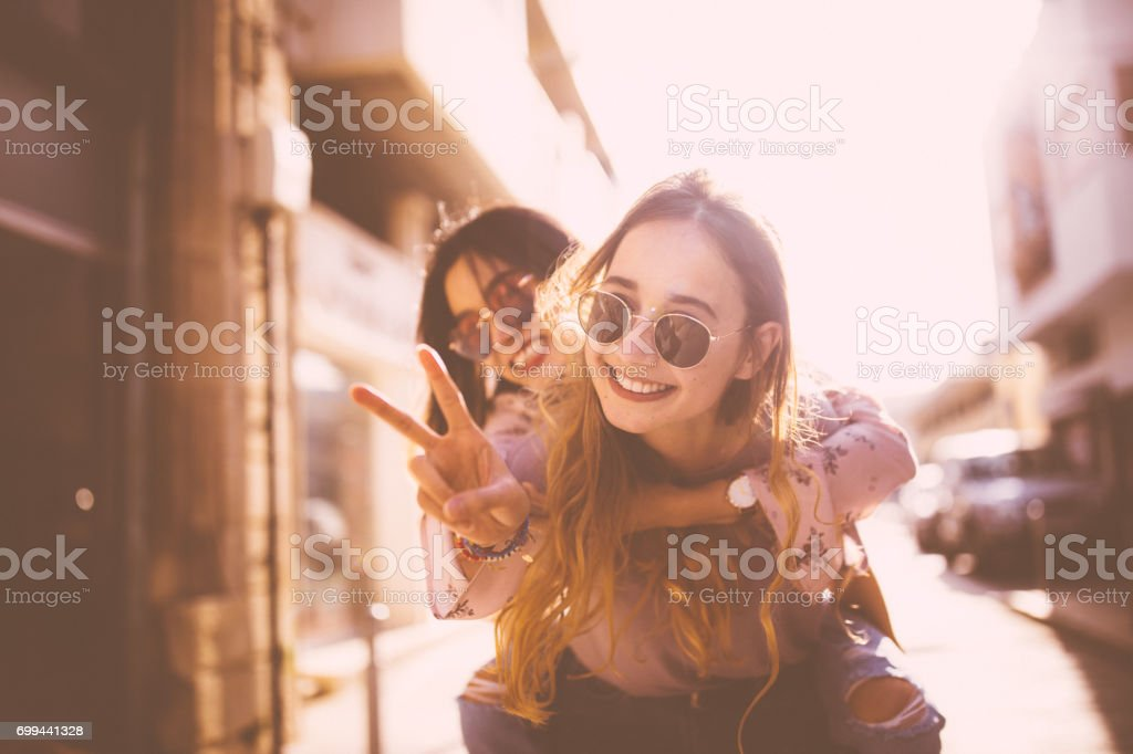 Young woman on piggyback ride doing the peace sign
