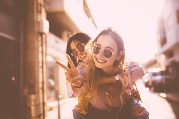 Young woman on piggyback ride doing the peace sign stock photo