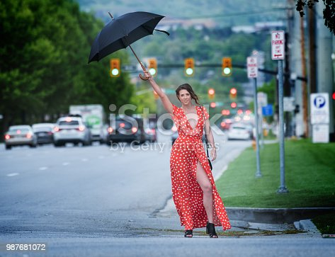 Young woman on road American zebra crossing, playing with umbrella in the rain