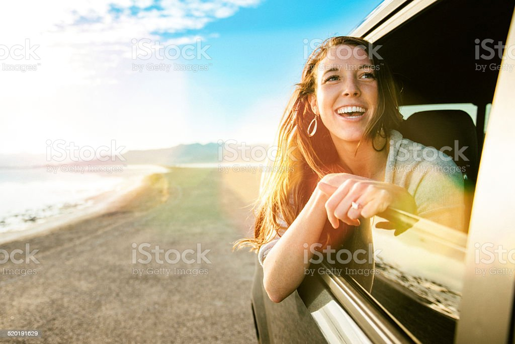 Young woman on road trip looking out the car window stock photo