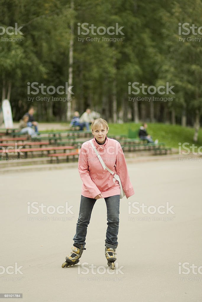 Young woman on roller blades in the park royalty-free stock photo