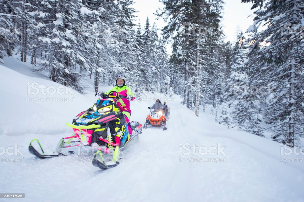 Young woman on snowmobiling tour in the frozen forest. stock photo