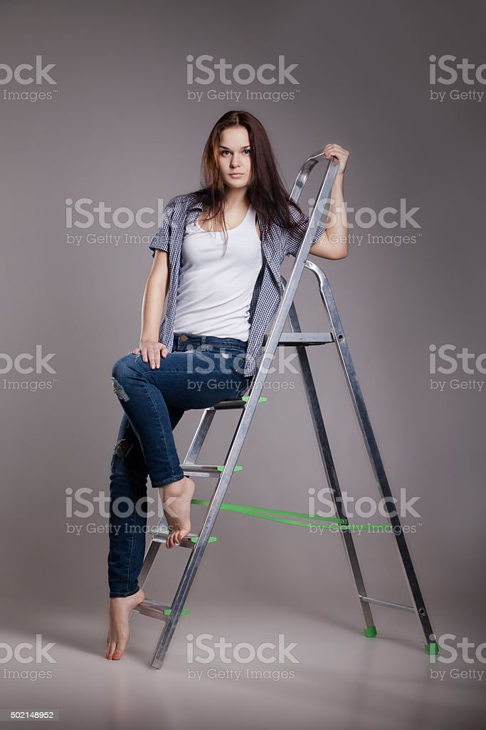 Young woman on step ladder stock photo