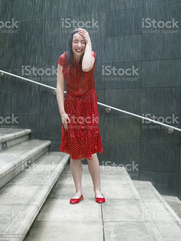 Young woman on steps in rain, hand resting on head, eyes closed stock photo