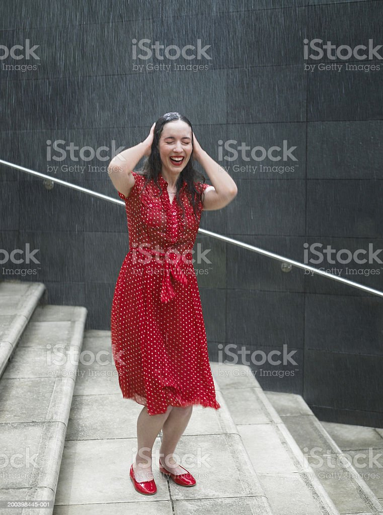 Young woman on steps in rain, hands resting on head, eyes closed, smiling stock photo