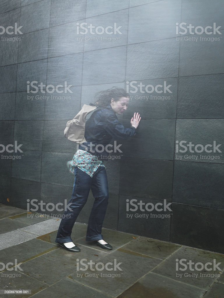 Young woman on street caught in rainstorm, eyes closed stock photo