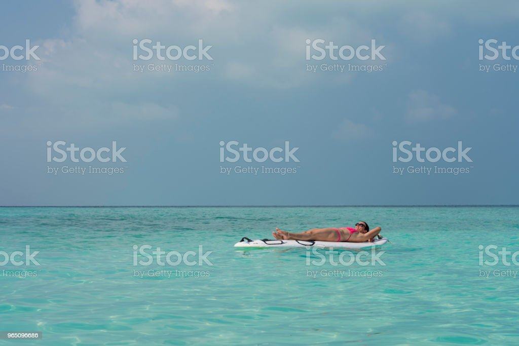 Young Woman on surfboard in the turquois sea zbiór zdjęć royalty-free