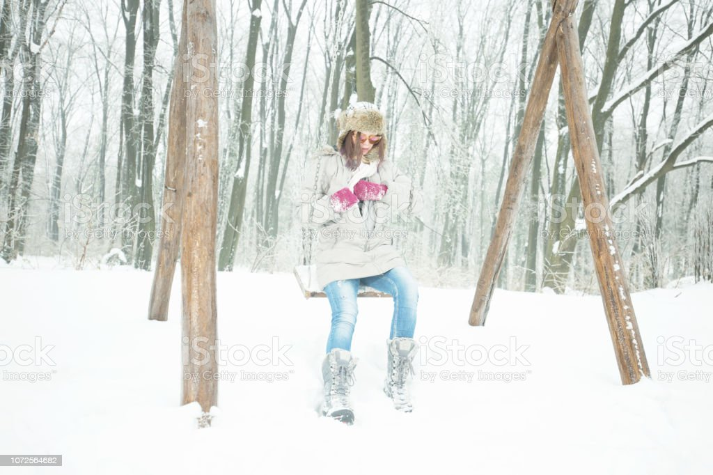 Young woman on swing in winter outdoors stock photo