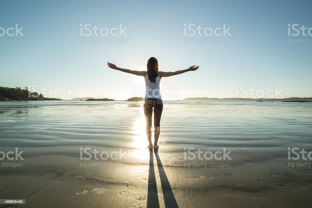 Young woman on the beach in autumn arms outstretched stock photo
