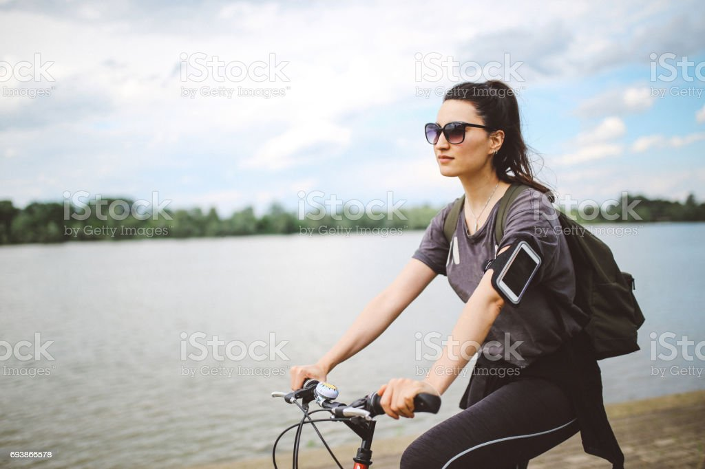 Young woman on the bicycle by the river stock photo