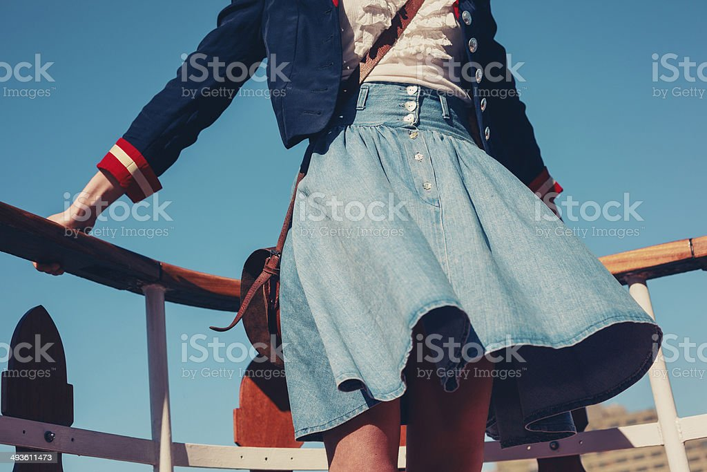 Young woman on the deck of ship with skirt blowing stock photo