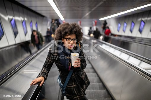 Young woman on the escalator drinking coffee to go