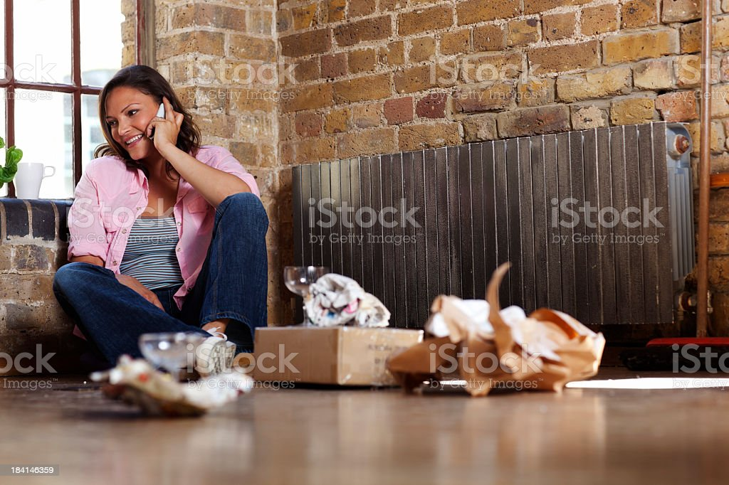 Young Woman on the Phone in a New Apartment royalty-free stock photo