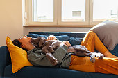Young woman lying on sofa with her weimaraner puppy on top of her, dog is licking its owner on the chin
