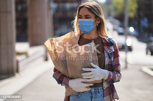 Young women wearing protective face mask and protective gloves to prevent Corona virus and other diseases, going home afrer shopping groceries, Covid-19 outbreak