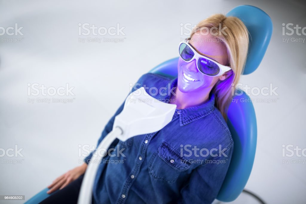 A young woman on the treatment of teeth whitening royalty-free stock photo