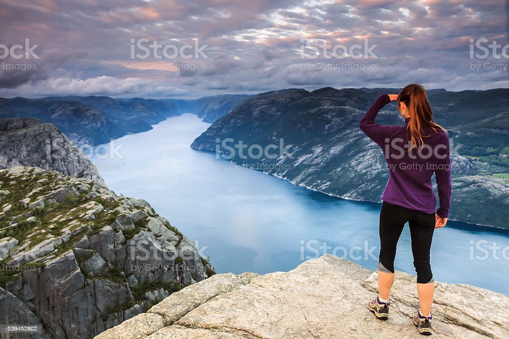 Young woman on top of a cliff stock photo