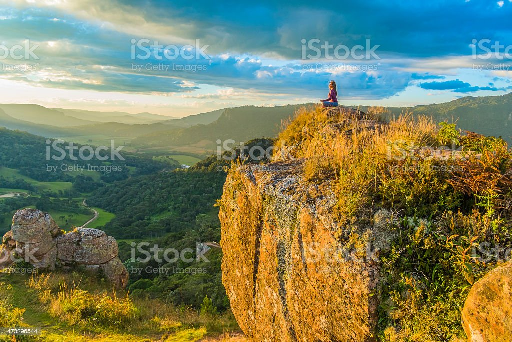 A young woman on top of a mountain doing yoga stock photo