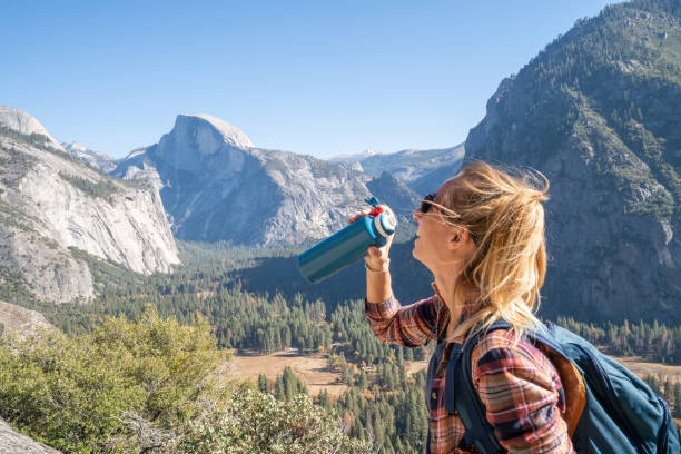 Young woman on top of Yosemite valley, USA drinking water from reusable bottle stock photo