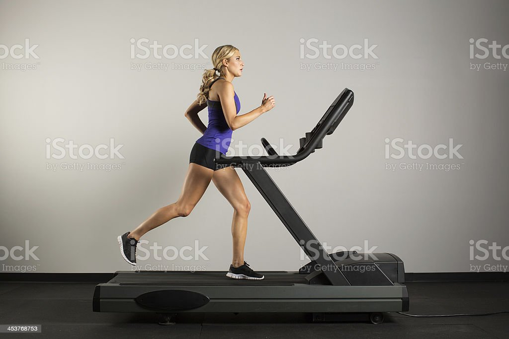 Young woman on treadmill stock photo