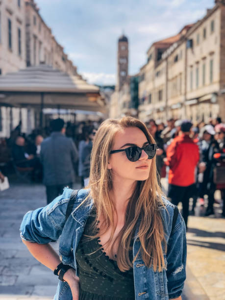 Young woman on vacation walking around the old town stock photo