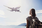 Young girl looking at the flying plane above the sea, travel concept