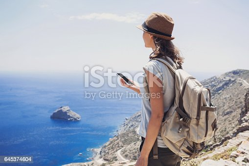 istock Young woman on vacations using smart phone 645374604