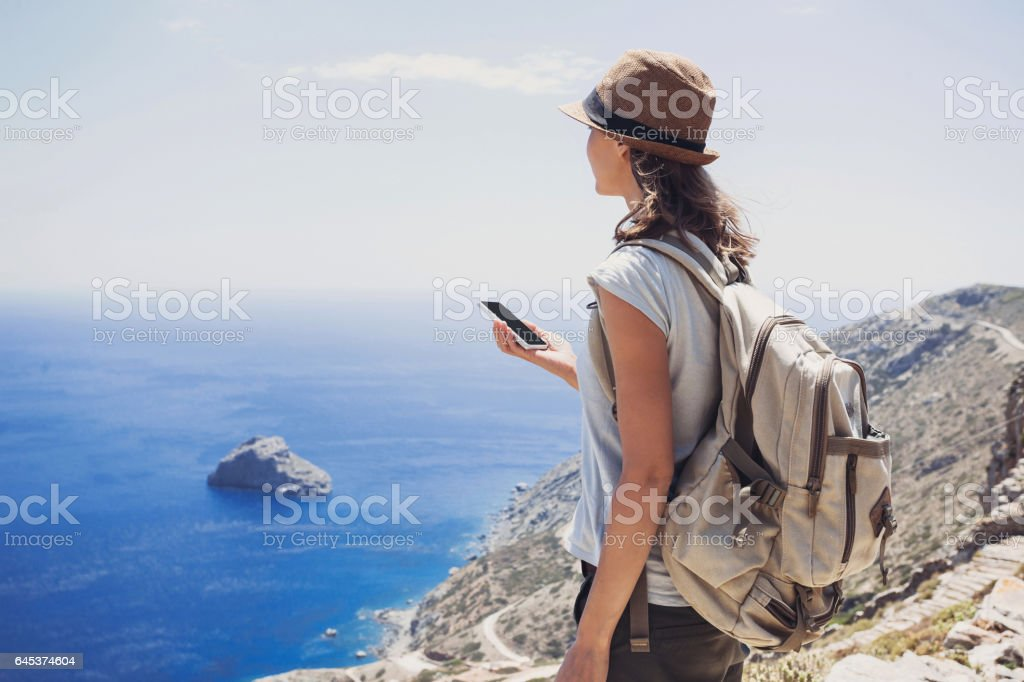 Young woman on vacations using smart phone stock photo